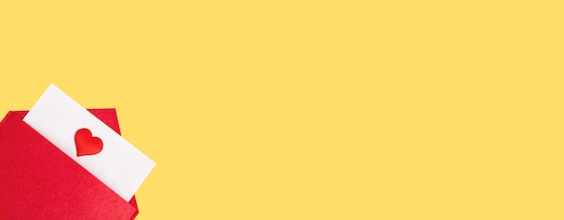 Envelope aberto de banner vermelho com uma folha de papel com um coração em um fundo amarelo