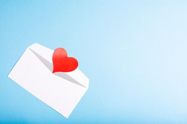 Envelope aberto e coração de papel vermelho sobre um fundo azul com lugar para texto