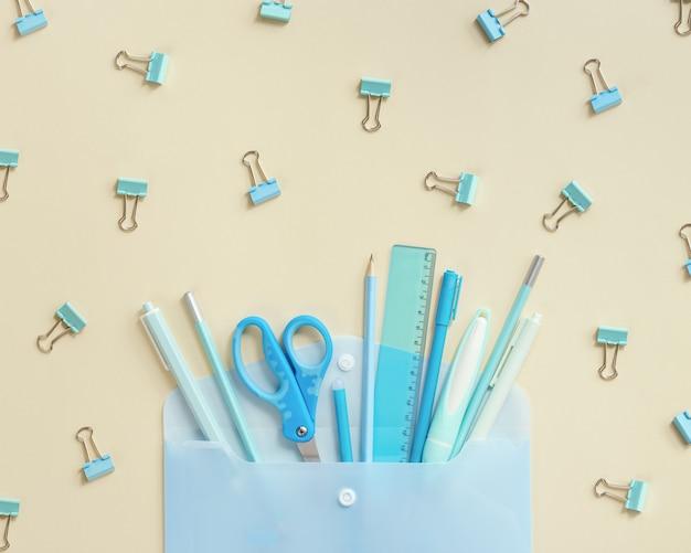 Envelope aberto e material escolar, lápis, canetas, réguas, tom azul