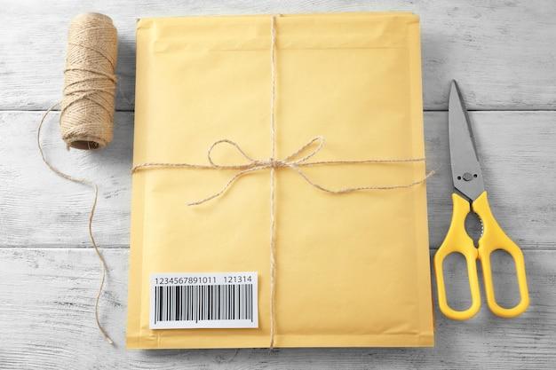 Envelope acolchoado para presente com número de rastreamento em fundo de madeira
