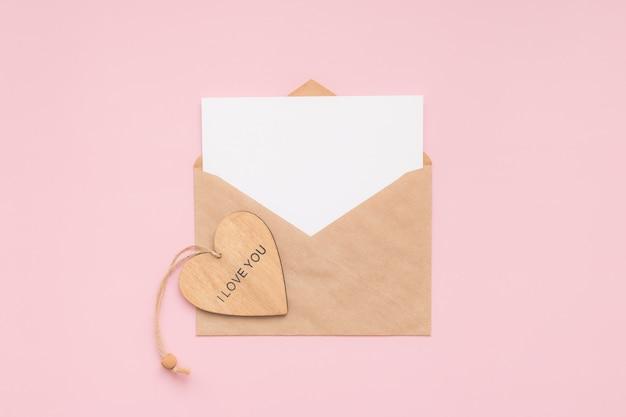 Envelope artesanal, cartão branco de papel em branco e coração de madeira com as palavras eu te amo em uma parede rosa. lugar para texto. postura plana. vista do topo. feliz dia dos namorados.