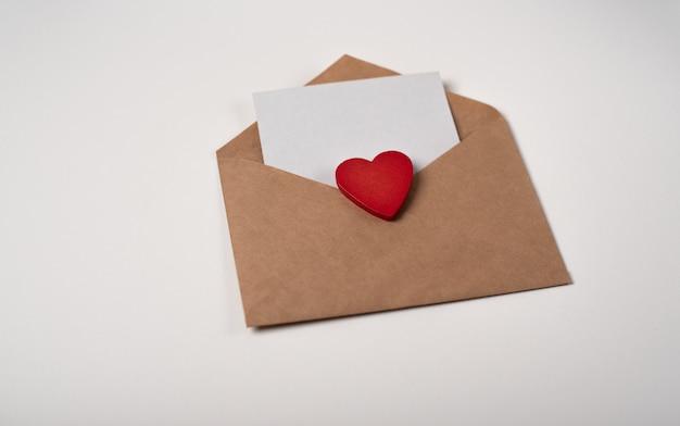 Envelope artesanal com uma folha de papel em branco e um coração de madeira vermelho. carta de amor romântico para o conceito de dia dos namorados.