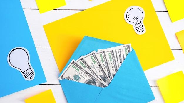 Envelope azul com dinheiro com papéis amarelos e azuis, ícones de lâmpada