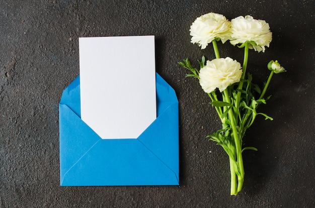 Envelope azul com papel branco em branco e buquê de flores brancas