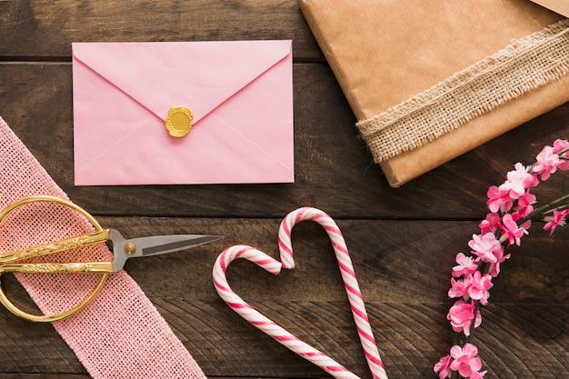 Envelope, bastões de doces, presentes e galhos com flores