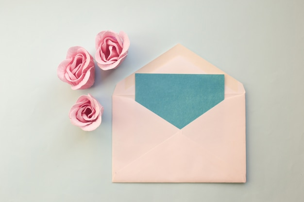 Envelope branco, cartão vazio azul, três flores cor-de-rosa cor-de-rosa em um fundo azul. mínimo plano
