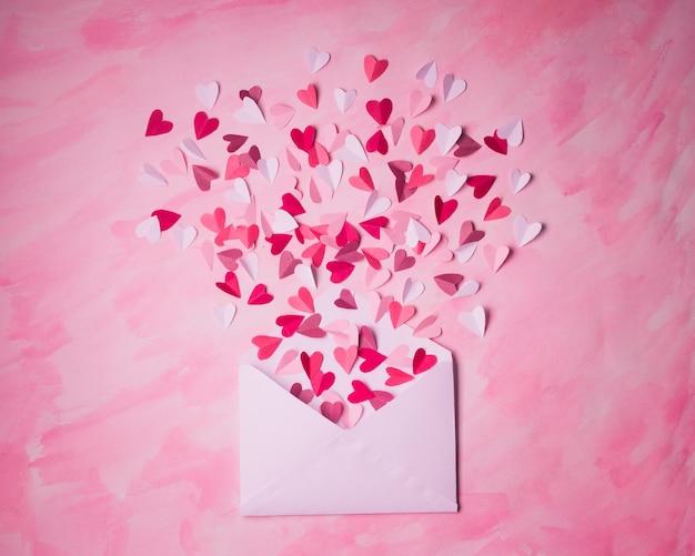 Envelope branco com corações de papel em um fundo rosa pintado. corações decolam de dentro do envelope aberto. carta de amor romântica.