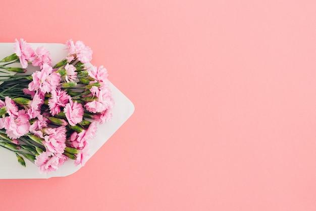 Envelope branco com flores cor de rosa na cor rosa. mail para você