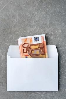 Envelope branco com notas de 50 euros.