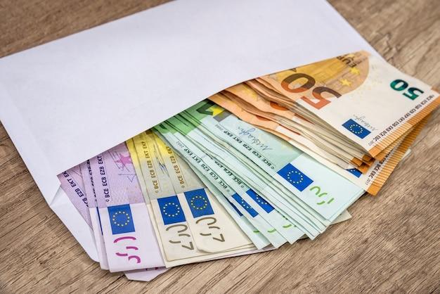Envelope branco com notas de euro sobre superfície de madeira