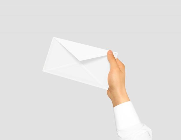 Envelope branco em branco simulado se segurando na mão.