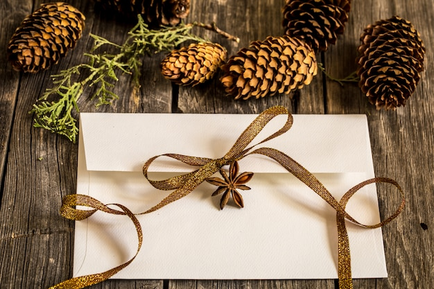 Envelope branco na parede de madeira com pinhas e presente de natal