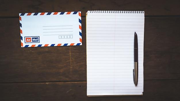 Envelope, caneta de tinta, papel em branco sobre uma mesa de madeira
