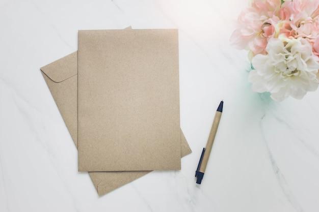 Envelope, caneta e flor no fundo branco da mesa de mármore.