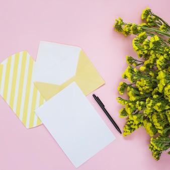 Envelope; cartão; caneta e flor amarela em fundo rosa