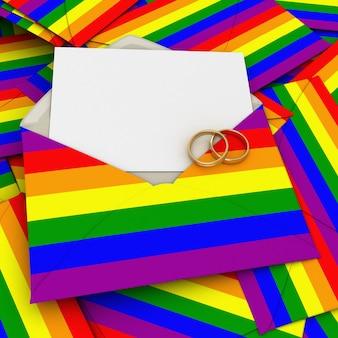 Envelope com a bandeira do arco-íris, um cartão em branco e duas alianças