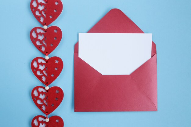 Envelope com cartão de presente branco em branco e decoração de corações vermelhos sobre fundo azul.