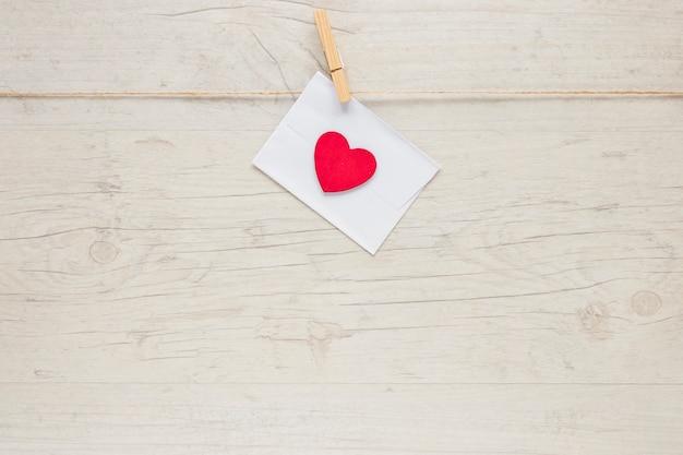 Envelope com coração pendurado na corda