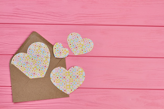 Envelope com corações de papel, copie o espaço. plano de fundo dia dos namorados com envelope artesanal e estatuetas em forma de coração em madeira rosa.