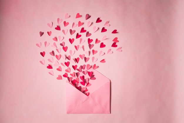 Envelope com corações de papel em um fundo rosa. corações decolam de dentro do envelope aberto. carta de amor romântica.