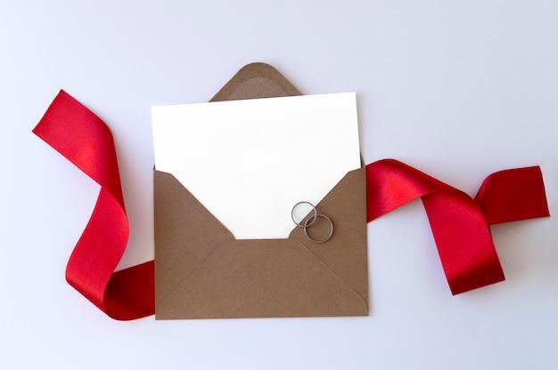 Envelope com fita vermelha e anéis