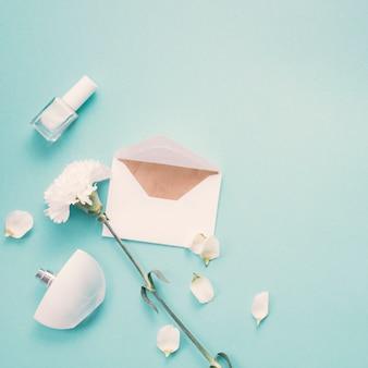 Envelope com flor branca e perfume na mesa azul