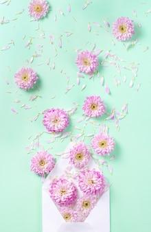 Envelope com flores e pétalas em um fundo rosa pastel