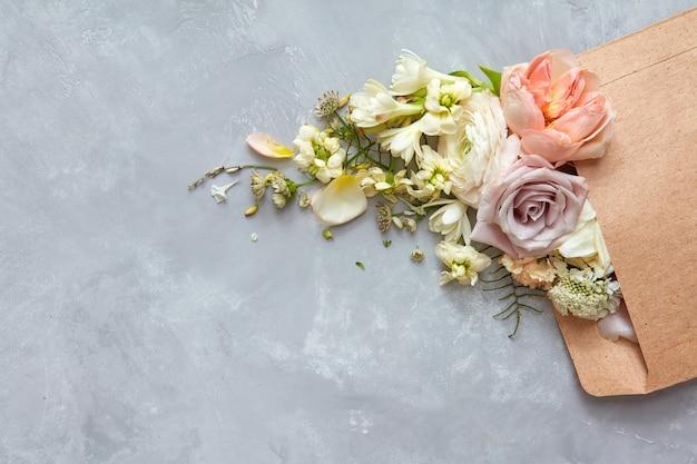 Envelope com flores no fundo cinza de pedra. postura plana