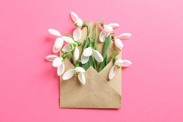 Envelope com flores snowdrop na cor de fundo, espaço para texto