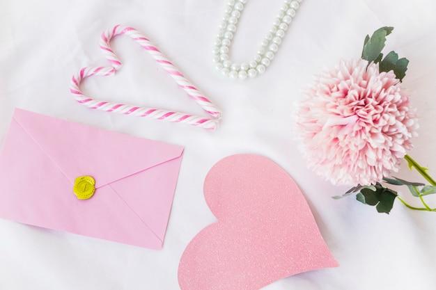 Envelope com grande coração de papel rosa na mesa