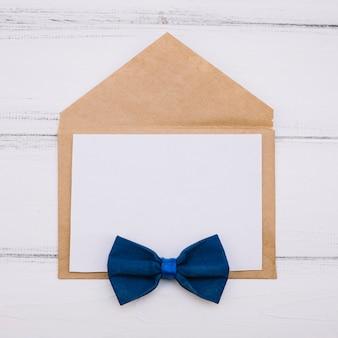 Envelope com papel e gravata borboleta