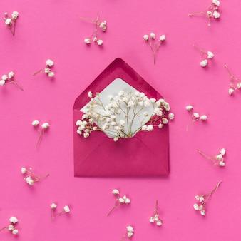 Envelope com pequenos ramos de flores na mesa
