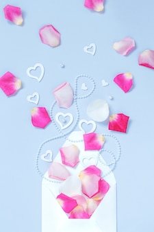 Envelope com pétalas e corações em um fundo pastel