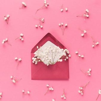 Envelope com ramos de flores brancas na mesa