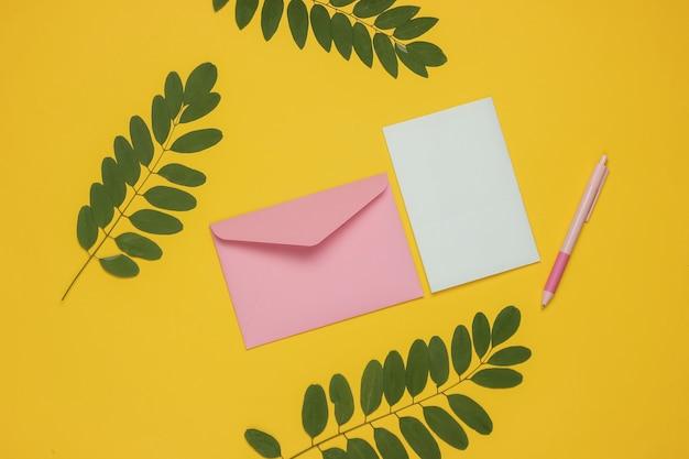 Envelope com uma carta e uma caneta em fundo amarelo com folhas verdes. dia dos namorados, casamento ou aniversário. vista do topo