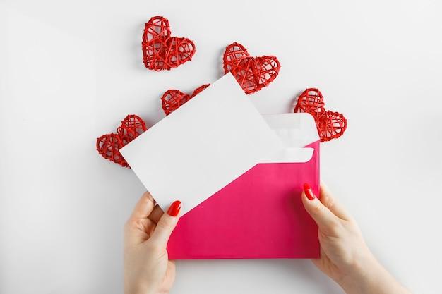 Envelope com uma carta nas mãos sobre um fundo branco. envelope rosa nas mãos e coração vermelho
