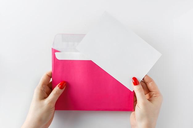 Envelope com uma carta nas mãos sobre um fundo branco. envelope rosa nas mãos em um fundo branco. folha em branco - conceito de design. carta de felicitações ao feriado.