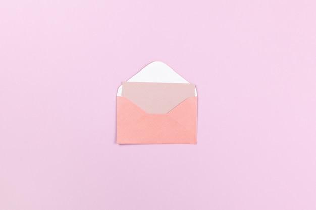 Envelope coral pequeno com cartão vazio dentro sobre fundo lilás
