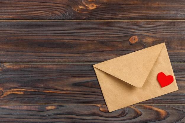 Envelope da carta de amor com coração vermelho no fundo de madeira.