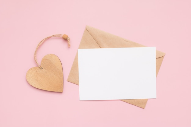Envelope de artesanato, cartão branco de papel em branco e coração de madeira em uma parede rosa. lugar para texto. postura plana. vista do topo. feliz dia dos namorados.