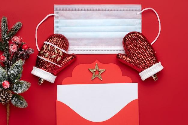 Envelope de carta vermelha de natal com espaço para texto em um fundo vermelho, bem como uma máscara médica como um símbolo de segurança
