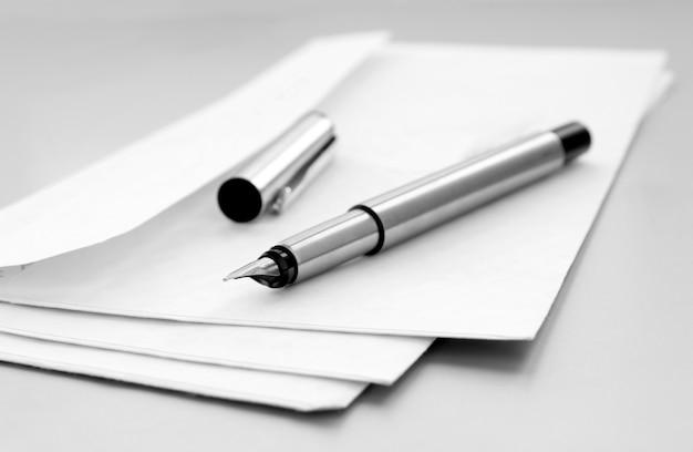 Envelope de correio e caneta em cima da mesa