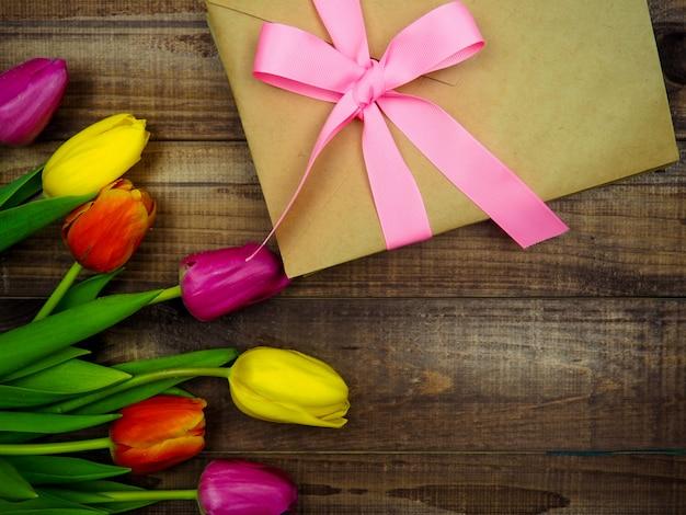 Envelope de kraft amarrado com uma fita rosa em fundo de madeira com tulipas