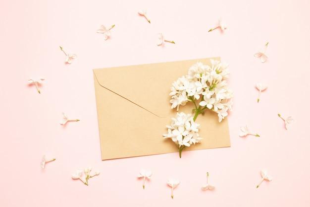 Envelope de maquete com ramos de lilás em um fundo rosa