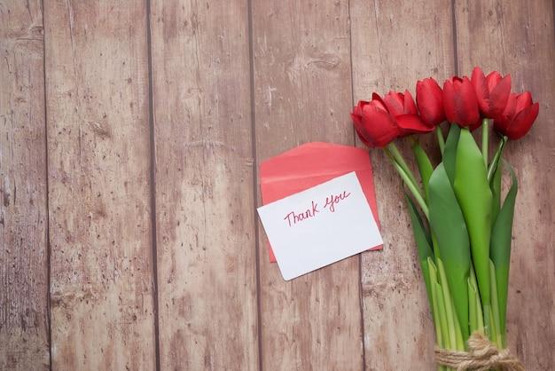 Envelope de mensagem de agradecimento e flor tulipa vermelha em fundo de madeira