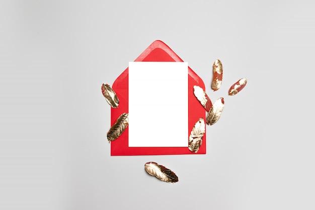 Envelope de negócios vermelho com folhas de papel branco e ouro sobre um fundo cinza.