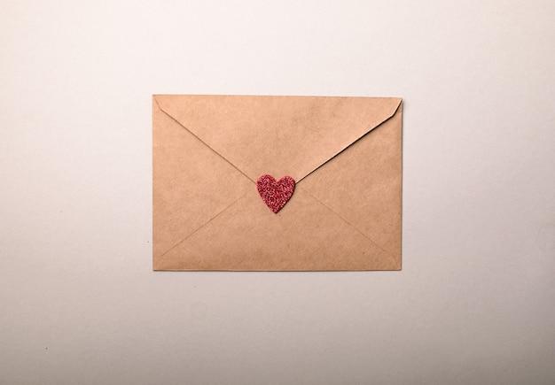 Envelope de papel com corações do dia dos namorados em fundo cinza. camada plana, vista superior. carta de amor romântico para o conceito de dia dos namorados.