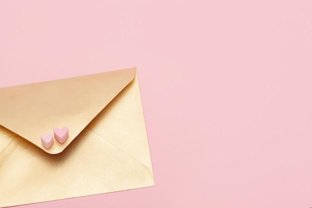Envelope de papel dourado com dois corações de marshmallow isolado em fundo rosa