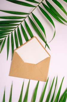 Envelope de papel kraft marrom com branco cartão vazio em folhas de palmeira, fundo branco, carta em branco maquete