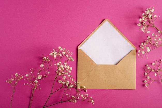 Envelope de papel kraft marrom com cartão branco vazio, flores gypsophila, fundo rosa roxo, carta em branco maquete